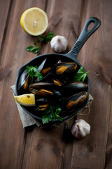 Frying pan with boiled mussels over dark wooden background