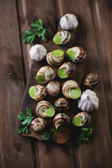 Bourgogne snails with garlic butter, rustic wooden background