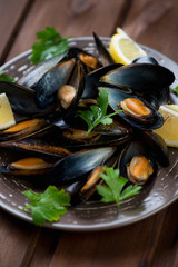 Boiled mussels with parsley and lemon, close-up, vertical shot