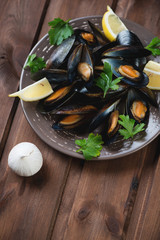 Still life with boiled mussels, wooden background, studio shot
