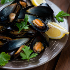 Close-up of steamed mussels served with fresh parsley and lemon
