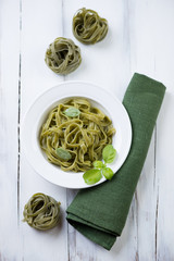 Green tagliatelle over white wooden background, above view