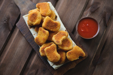 Chicken nuggets with dip sauce over rustic wooden background