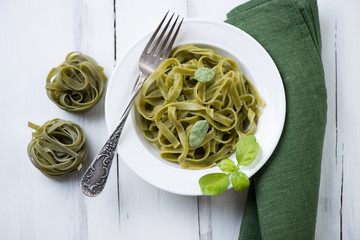 Glass plate with green tagliatelle and basil, high angle view