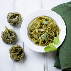 Tagliatelle with green basil over white wooden surface