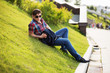 Young fashion man in sunglasses sitting on the grass in a city p