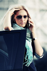 Fashion business woman calling on the phone at the car