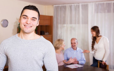 smiling guy and big family with agent at distance indoor