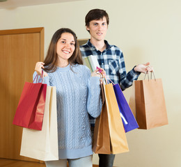 Happy guy and girl holding purchases in hands