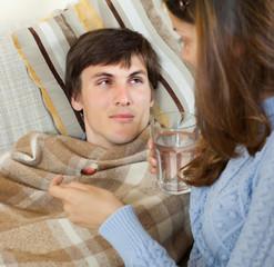 woman giving medicinal syrup to  husband