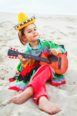 Toned photo of Little happy smiling boy plays his guitar or
