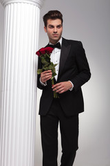 business man holding bouquet of red roses in his hand