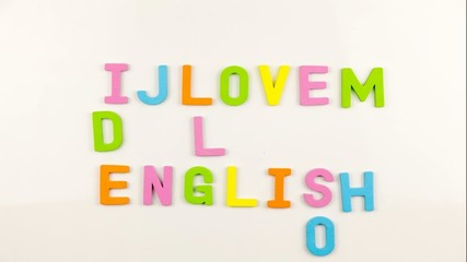 Alphabet magnets being taken away to form I Love English