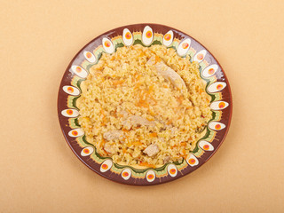 Pilaf dish, bulgur wheat with meat on ceramic plate