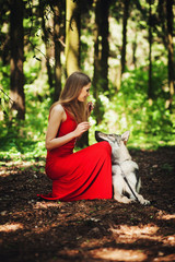 young woman playing with the dog in the forest