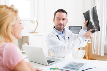 Young attractive doctor analysing X-ray with patient