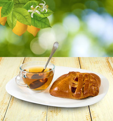 cup of tea and buns on a table on a green background