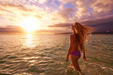 Carefree woman in the sunset on the beach.