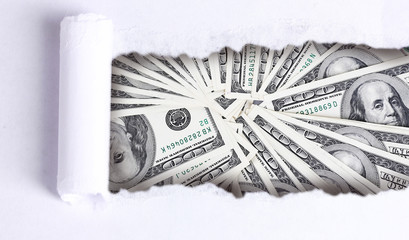 Dollar banknotes through torn white paper
