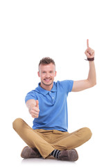 young casual man points up and gives thumb up