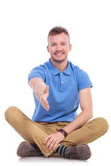 seated young casual man offers handshake