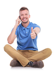 young casual man on the phone shows thumb up