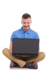 seated young man works on laptop