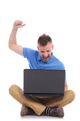 seated young casual man cheers with laptop