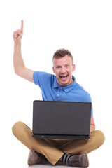young seated man with laptop points up