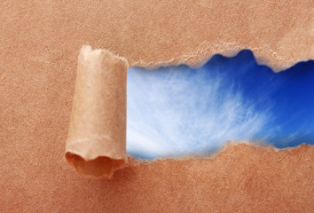 Blue sky background with clouds through torn craft paper