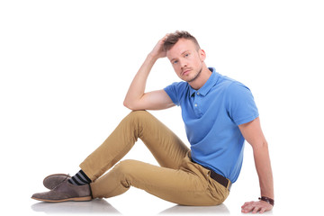 pensive young man sitting on the floor