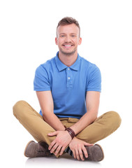 seated young casual man smiles at camera