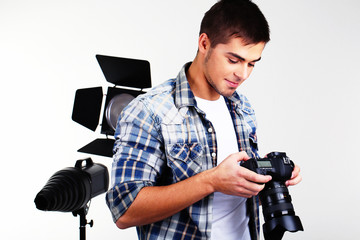 Handsome photographer with camera in photo studio