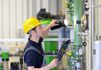 Handwerker überprüft Industrieanlage-Heizung / industrial worker