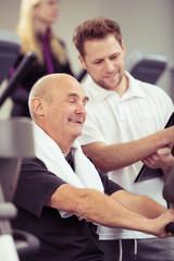 trainer erklärt einem älteren mann das fitness-gerät