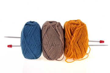 Trois pelotes de laine et aiguilles à tricoter