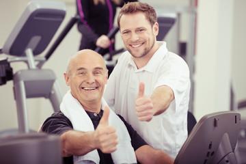 trainer und älterer kunde zeigen daumen hoch im sportstudio