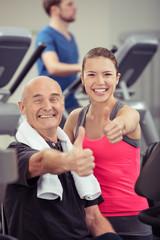 senior und junge frau zeigen daumen hoch im fitness-studio