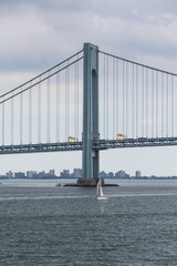 White Sailboat Under Suspension Bridge