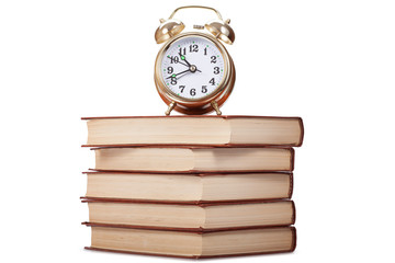 Gold alarm clock stand on a pile of books, a white background