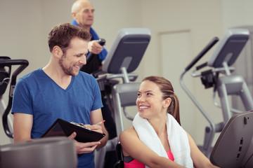 trainer und zufriedene kundin im fitness-club