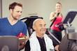 trainer und älterer mann im fitness-studio