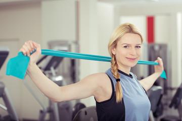 lächelnde frau trainiert mit einem gymnastik-band im studio