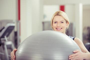 lächelnde frau mit gymnastik-ball im fitnessraum