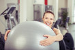 lachende frau mit ball im fitness-studio