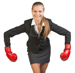Businesswoman wearing boxing gloves bending forward with her