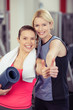 frauen im fitness-studio zeigen daumen hoch