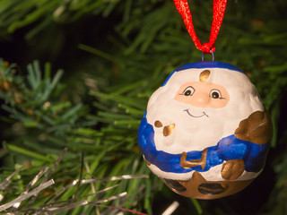 blue santa claus shaped ball decoration on christmas tree