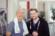 trainer betreut einen älteren sportler im fitness-studio