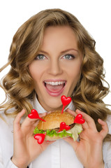 Smiling young woman with hamburger from hearts